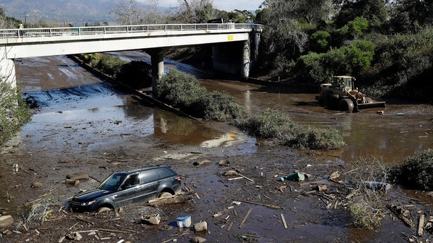 FILE - In this Wednesday, Jan. 10, 2018 file photo, a bulldozer moves debris as a vehicle sits stranded in flooded water on U.S. Highway 101 in Montecito, Calif. The California mudslide that killed at least 18 people is causing distress miles from where the torrent of muck and boulders stopped, as a local economy that thrives on tourism and the lure of sun-soaked beaches was left reeling. (AP Photo/Marcio Jose Sanchez)
