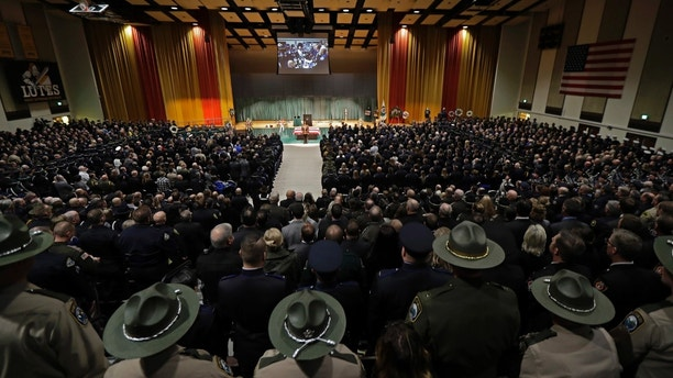 Law enforcement and other officials stand during a memorial service for slain Pierce County Sheriff's Deputy Daniel McCartney, Wednesday, Jan. 17, 2018, at Pacific Lutheran University in Tacoma, Wash. McCartney died the night of Sunday, Jan. 7, 2018, after being shot while responding to a to a break-in call southeast of Tacoma. (AP Photo/Ted S. Warren, Pool)