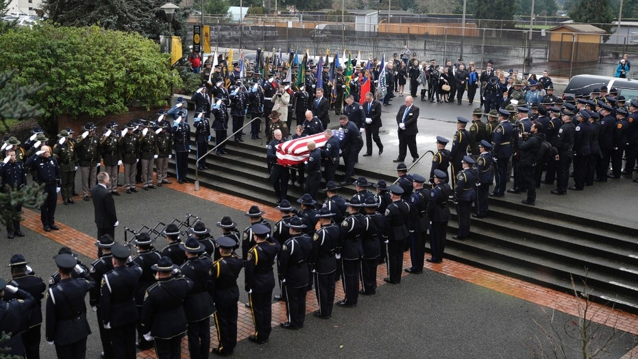 Law enforcement and other officials salute as the flag-draped coffin of slain Pierce County Sheriff's Deputy Daniel McCartney is carried by pall bearers prior to a memorial service at Pacific Lutheran University in Tacoma, Wash.
