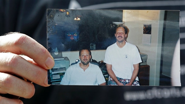 FILE - In this Oct. 2, 2017 file photo, Eric Paddock holds a photo of himself, at left, and his brother, Las Vegas shooter Stephen Paddock, at right, outside his home in Orlando, Fla. Officials in Las Vegas say the cremated remains of the gunman in the worst mass shooting in modern U.S. history have been turned over to his brother. Clark County Coroner John Fudenberg said in a statement that Stephen Paddock's ashes were given to Paddock's brother, Eric Paddock, Thursday, Jan. 18, 2017. (AP Photo/John Raoux, File)