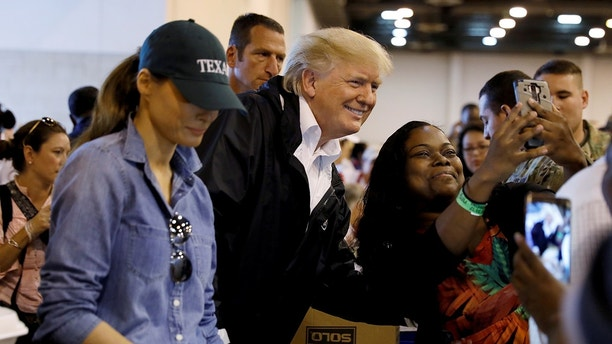 "U.S. President Donald Trump poses for a photo as he and first lady Melania Trump help volunteers hand out meals during a visit with flood survivors of Hurricane Harvey at a relief centre in Houston, Texas, U.S., September 2, 2017. Kevin Lamarque: ""Trump, eager to deliver the image of a hands-on response to Hurricane Harvey, made this visit to a relief centre and obliged this woman with a selfie as Melania continued to work."" REUTERS/Kevin Lamarque/File Photo  Kevin SEARCH ""POY TRUMP"" FOR THIS STORY. SEARCH ""REUTERS POY"" FOR ALL BEST OF 2017 PACKAGES.    TPX IMAGES OF THE DAY - RC1735C6E200"