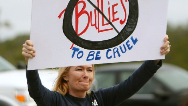 In this Monday, Jan. 22, 2018 photo, Dawn Graff holds a sign to protest bullying with other concerned parents and family members near Surfside Middle School, in Panama City Beach, Fla. Two 12-year-olds in Florida have been charged with cyberstalking in connection with the death of a student at the middle school, who police say hanged herself two weeks ago. (Patti Blake/News Herald via AP)