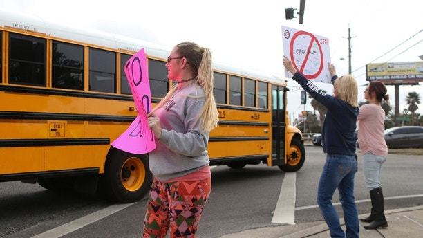 "In this Monday, Jan. 22, 2018 photo, Kelli Martin, left, holds a sign with ""Say No to Bullying"" written across it as a school bus drives past during a protest by concerned parents and family members against bullying near Surfside Middle School, in Panama City Beach, Fla. Two 12-year-olds in Florida have been charged with cyberstalking in connection with the death of a student at the middle school, who police say hanged herself two weeks ago.  (Patti Blake/News Herald via AP)"