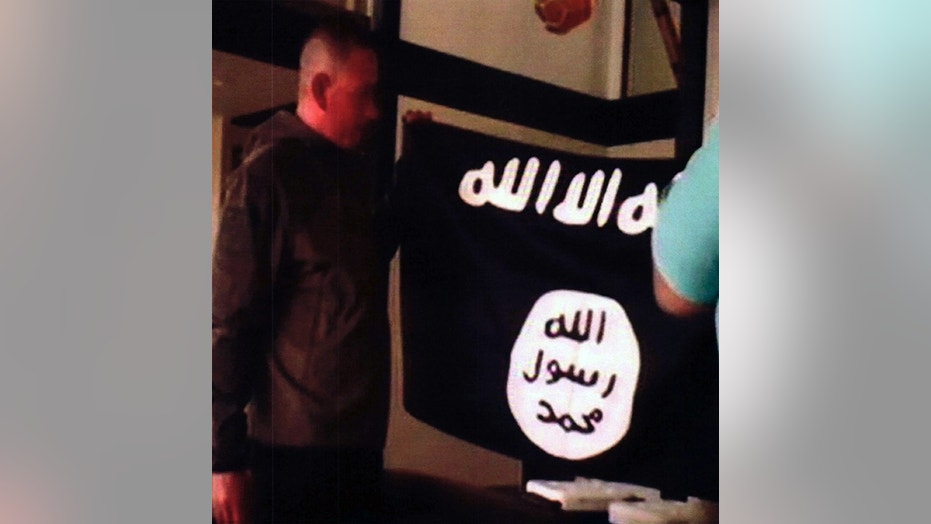 Army Sgt. 1st Class Ikaika Kang holds an ISIS flag after allegedly pledging allegiance to the terror group at a house in Honolulu this past July.