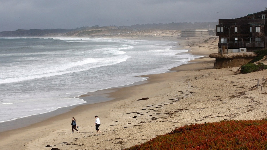 Beachgoers ignore the beach closure signs posted at Monterey State Beach in Monterey, Calif., Jan. 22, 2018.