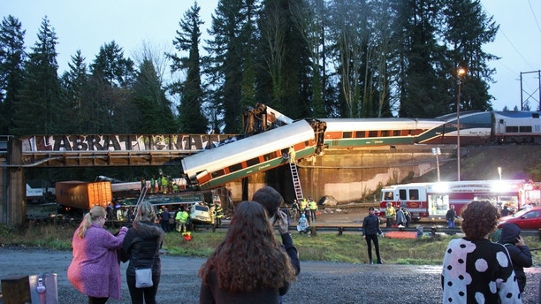 In this photo provided by Daniella Fenelon, first responders work at the scene of an Amtrak train that derailed in DuPont, south of Seattle on Monday, Dec. 18, 2017. The Amtrak train making the first-ever run along a faster new route hurtled off an overpass south of Seattle and spilled some of its cars onto the highway below, killing some people, injuring dozens and crushing a few vehicles, authorities said. Fenelon was a passenger of the train. (Daniella Fenelon via AP)