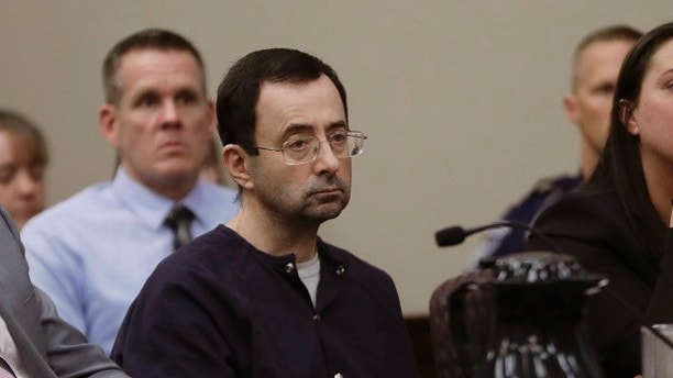 "Larry Nassar sits during his sentencing hearing Wednesday, Jan. 24, 2018, in Lansing, Mich.  The former sports doctor who admitted molesting some of the nation's top gymnasts for years was sentenced Wednesday to 40 to 175 years in prison as the judge declared: ""I just signed your death warrant.""  The sentence capped a remarkable seven-day hearing in which scores of Nassar's victims were able to confront him face to face in the Michigan courtroom.  (AP Photo/Carlos Osorio)"