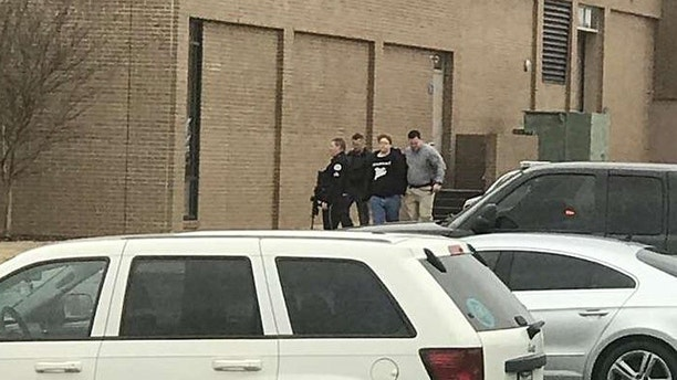 UPDATES TO REMOVE NUMBER OF PEOPLE INJURED - Police escort a person, second from right, out of the Marshall County High School after shooting there, Tuesday, Jan 23, 2018, in Benton, Ky.  Gov. Matt Bevin said two people were killed numerous others were injured in the shooting. (Dominico Caporali via AP)