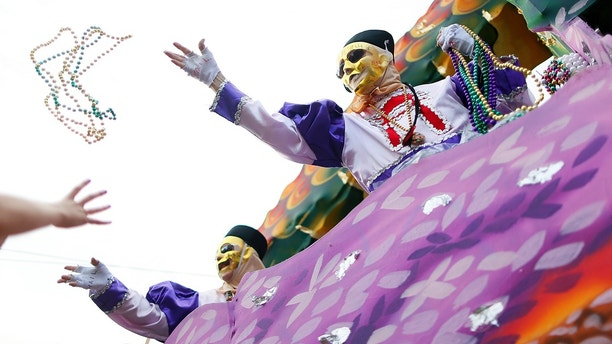 A member of the Krewe of Thoth throws beads during a Mardi Gras parade in New Orleans, Louisiana February 15, 2015. REUTERS/Jonathan Bachman (UNITED STATES - Tags: SOCIETY) - GM1EB2G0NWZ01