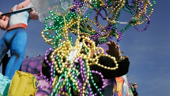 A parade rider throws out beads during the Knights of Nemesis Mardi Gras parade in Chalmette, St. Bernard Parish, Louisiana February 11, 2007. REUTERS/Lee Celano (UNITED STATES) - GM1DUPANUIAA