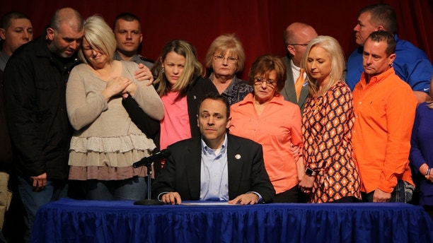 The parents of the late 15-year-old Bailey Holt, left, mourn while Kentucky Governor Matt Bevin signs the proclamation of the prayer on Friday, January. 26, 2018 in Benton, Kentucky. Marshall County High School reopened its doors Frida and as the school day began with an assembly. Police say two students were killed, 14 were injured by gunfire and another seven suffered other injuries when the boy opened fire at the school on Tuesday before the classes began. (AP Photo / Robert Ray)