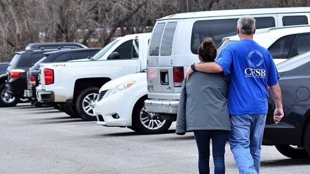 Family members escort their children out of Marshal North Middle School near Palma, Ky., Tuesday, Jan. 23, 2018, after the students where transported from Marshal High School. The students were transported to the middle school to be picked up by family members after a deadly shooting at the high school. (AP Photo/Stephen Lance Dennee)
