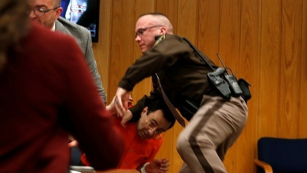 An Eaton County Sheriff protects Larry Nassar, (wearing orange) a former team USA Gymnastics doctor who pleaded guilty in November 2017 to sexual assault charges, as he is attacked by Randall Margraves (not pictured) during victim statements of his sentencing in the Eaton County Circuit Court in Charlotte, Michigan, U.S., February 2, 2018.   REUTERS/Rebecca Cook - RC1A5DD58700