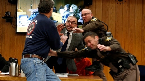 Randall Margraves (L) lunges at Larry Nassar,(wearing orange) a former team USA Gymnastics doctor who pleaded guilty in November 2017 to sexual assault charges, during victim statements of his sentencing in the Eaton County Circuit Court in Charlotte, Michigan, U.S., February 2, 2018.   REUTERS/Rebecca Cook - RC1495A64ED0