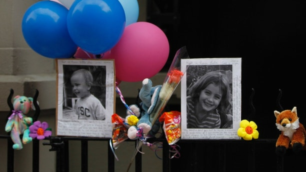 Photographs of the two children allegedly stabbed by their nanny are displayed alongside balloons and stuffed animals at a memorial outside the apartment building were they lived, Saturday, Oct. 27, 2012, in New York. The 2-year-old son and 6-year-old daughter of a CNBC executive were found dead by their mother in a dry bathtub in the family's Upper West Side apartment Thursday night. The nanny suspected of stabbing the children was in critical condition Friday with apparently self-inflicted injuries. (AP Photo/Mary Altaffer)