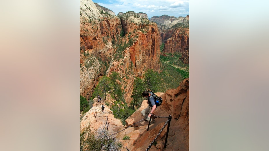 Hikers climb down the Angels Landing trail in Zion National Park, in Utah. Zion National Park officials say a 13-year-old girl has fallen to her death from a popular narrow trail bordered by steep drops.