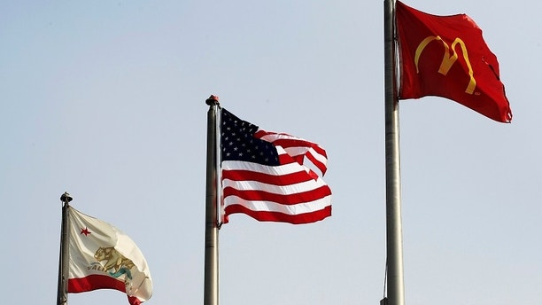 A United States flag (C) flies between the state flag of California (L) and a McDonald's restaurant flag at the border in San Ysidro, California September 27, 2011. With over 13 million vehicles a year, 24 lanes of traffic and 18,000 pedestrians a day, the task of risk management happens 24 hours a day, seven days a week at the U.S.-Mexican border in San Ysidro, California. Hundreds of customs and border protection officers use sophisticated technology to protect the busiest land border crossing in the U.S. The world's population is projected to reach 7 billion on October 31, 2011, according to official U.N. population projections, presenting what the United Nations Population Fund called both a challenge and an opportunity. Picture taken September 27, 2011. REUTERS/Mike Blake (UNITED STATES - Tags: TRANSPORT POLITICS BUSINESS FOOD) - GM1E7A71O6I01