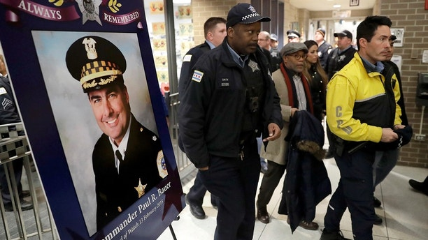 Chicago police officers pass a memorial portrait of Cmdr. Paul Bauer for a candlelight vigil for Bauer outside the Near North District headquarters Wednesday, Feb. 14, 2018, in Chicago. The 53-year-old Bauer, who had been with the department 31 years, was fatally shot as he went to assist other officers who were pursuing the suspect, Shomari Legghette, in downtown Chicago on Tuesday. Legghette is charged with first-degree murder in the shooting of Bauer. (AP Photo/Charles Rex Arbogast)