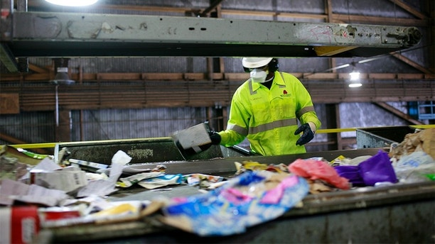 An employee at Recology sorts refuse at the company's facility in San Francisco, California November 2, 2009. Each day the company, bought by its employees through an Employee Stock Ownership Plan (ESOP), takes in more than 750 tons of plastic, paper and glass, sorts the trash and presses the materials into compact cubes.  Picture taken November 2, 2009. To match feature CLIMATE/CITIES   REUTERS/Robert Galbraith  (UNITED STATES ENVIRONMENT SOCIETY) - GM1E5BU0LQB01