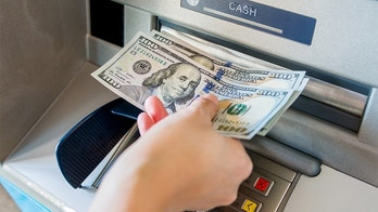 Woman hand taking money out of the ATM machine.