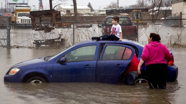 Flint resident Brayden Bend, 5, sits on top of his mother's friend's vehicle on Robert T. Longway Boulevard at North Center Road on Tuesday, Feb. 20, 2018, in Flint, Mich. High flood waters caused several motorists to become stuck. (Bronte Wittpenn/The Flint Journal-MLive.com via AP)