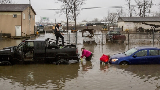 High floor waters caused several motorists to become stuck on Tuesday, Feb. 20, 2018, in Flint, Mich. High water from storm flooding closed roads in Michigan. (Bronte Wittpenn/The Flint Journal-MLive.com via AP)