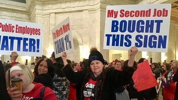 Gloria Triplett, a reading specialist at East Chapmanville Elementary School, holds signs Friday, Feb. 2, 2018, during a teacher rally at the West Virginia Capitol in Charleston, W.Va. Hundreds of teachers from at least three counties held a one-day walkout in order to rally for pay raises and better health benefits. (AP Photo/John Raby)