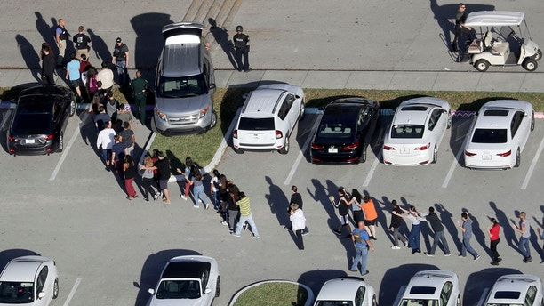 FILE - In this Feb. 14, 2018 file photo, students are evacuated by police from Marjory Stoneman Douglas High School in Parkland, Fla., after a shooter opened fire on the campus. The school shooting that left several people dead appears to be the first major tragedy of its kind in which students were sharing horrific images in near-real time with young people elsewhere. Experts say the footage could scar young people psychologically. But it could also galvanize them.  (Mike Stocker/South Florida Sun-Sentinel via AP)