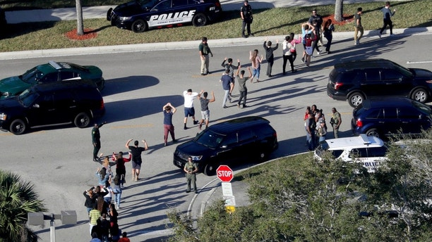 FILE - In this Wednesday, Feb. 14, 2018 file photo, students hold their hands in the air as they are evacuated by police from Marjory Stoneman Douglas High School in Parkland, Fla., after a shooter opened fire on the campus. A week after a shooter slaughtered more than a dozen people in the Florida high school, thousands of protesters, including many angry teenagers, swarmed into the state Capitol on Wednesday, Feb. 21, calling for changes to gun laws, a ban on assault-type weapons and improved care for the mentally ill. (Mike Stocker/South Florida Sun-Sentinel via AP, File)