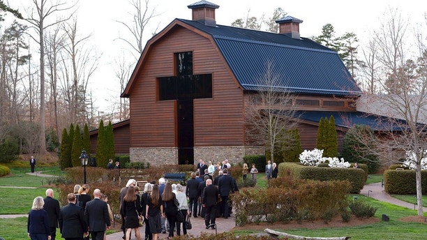 Pall bearers carry the casket carrying the body of Billy Graham as family member follow behind to the Billy Graham Library in Charlotte, N.C., Saturday, Feb. 24, 2018. Graham's body was brought to his hometown of Charlotte on Saturday, Feb. 24, as part of a procession expected to draw crowds of well-wishers. (Jeff Siner/The Charlotte Observer via AP)