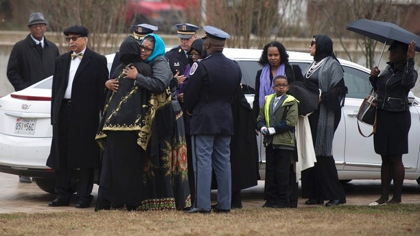 Family and friends embrace during a memorial service for Prince George's County police officer Mujahid Ramzziiddin, Friday, Feb. 23, 2018 at the Diyanet Center of America in Lanham, Md. Prince George's County police say 37-year-old Glenn Tyndell shot Cpl. Mujahid Ramzziddin five times with a shotgun Wednesday when the off-duty officer attempted to intervene in a dispute between Tyndell and his wife.(Marvin Joseph/The Washington Post via AP)