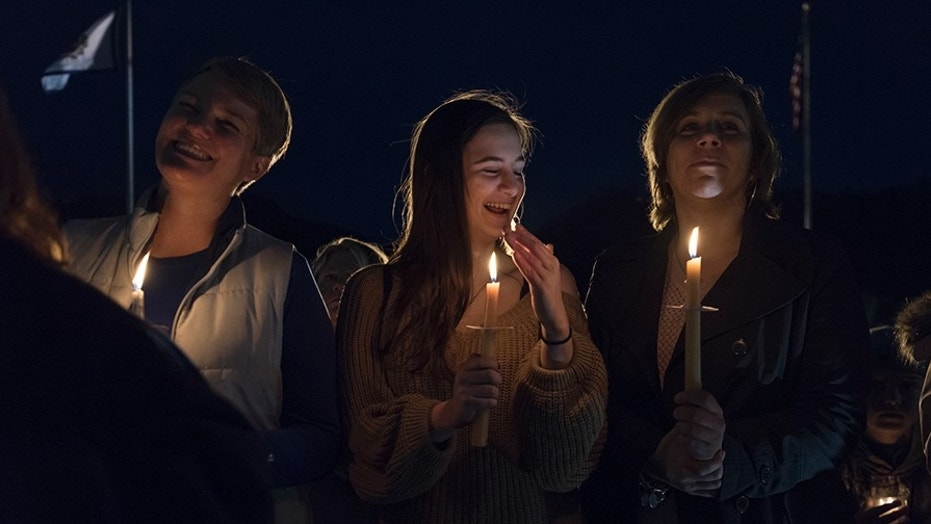 From left, Capital High School teacher Susie Garrison, George Washington High School student Amelia Engle and Nitro High School teacher Kizmet Chandler smiling during a candlelight rally in support of the ongoing statewide teachers walkout outside of the capitol building in Charleston, W.V., on Sunday.