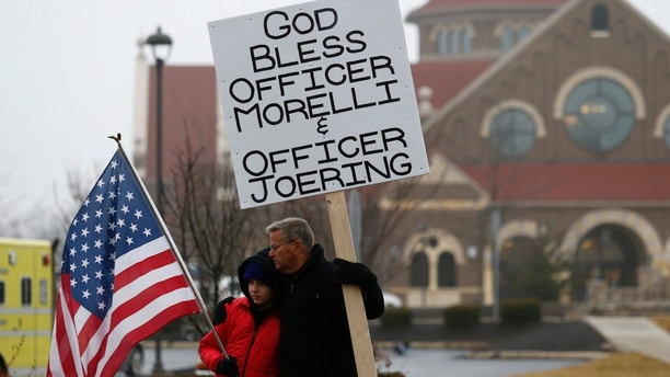 Bob Votruba, right, and his nephew Mason Miller, 13, stand outside of St. Paul the Apostle Catholic Church in in Westerville, Ohio, before the start of funeral services for Westerville police officers Anthony Morelli and Eric Joering at the church Friday, Feb. 16, 2018. The two veteran officers were shot after entering a residence early Saturday afternoon. (AP Photo/Paul Vernon)