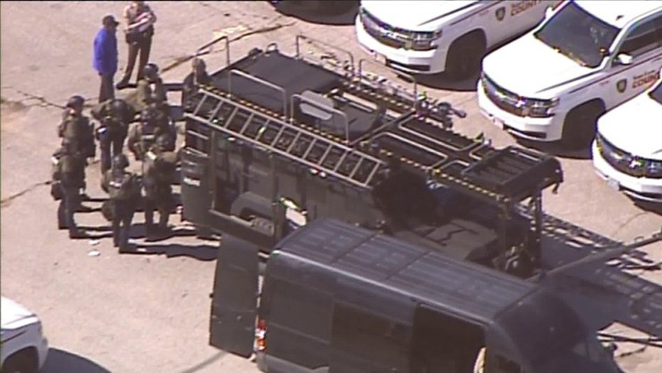 A SWAT team arrives amid a standoff in northeast St. Louis County with a gunman who shot a U.S. Marshal.