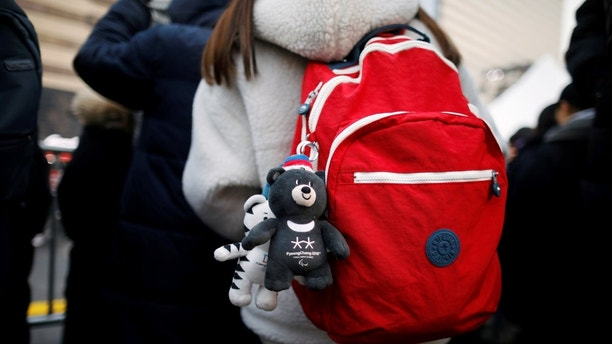 Plushies of the 2018 PyeongChang Winter Olympics mascot Soohorang and Paralympics mascot Bandabi hang on a backpack as spectators watch the Olympic torch relay in Seoul, South Korea, January 13, 2018.  REUTERS/Kim Hong-Ji - RC16C30FD7E0