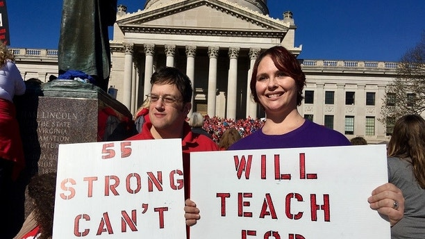 Teachers John and Kerry Guerini of Fayetteville, West Virginia, hold signs at a rally at the state Capitol in Charleston, W.Va., Monday, Feb. 26, 2018. Teachers across West Virginia will continue a walkout over pay and benefits for a fourth day. (AP Photo/John Raby)