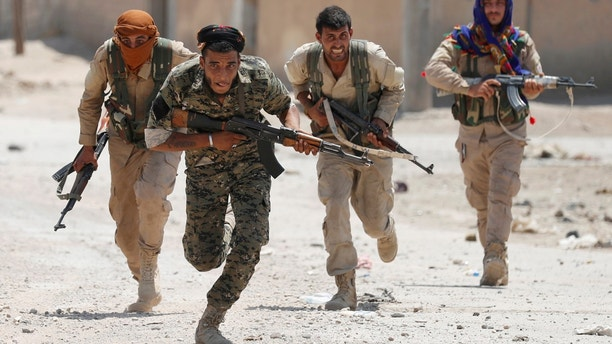 """Kurdish fighters from the People's Protection Units (YPG) run across a street in Raqqa, Syria, July 3, 2017. Goran Tomasevic: """"They were members of Kurdish YPG militia. They were running across the street because ISIS fighters' positions were nearby. I shot the picture in a last day of my assignment. I was lucky to have that picture as YPG fighters were giving very restricted access to media."""" REUTERS/ Goran Tomasevic/File Photo SEARCH """"POY IS"""" FOR THIS STORY. SEARCH """"REUTERS POY"""" FOR ALL BEST OF 2017 PACKAGES. TPX IMAGES OF THE DAY - RC164AFF4C20"""