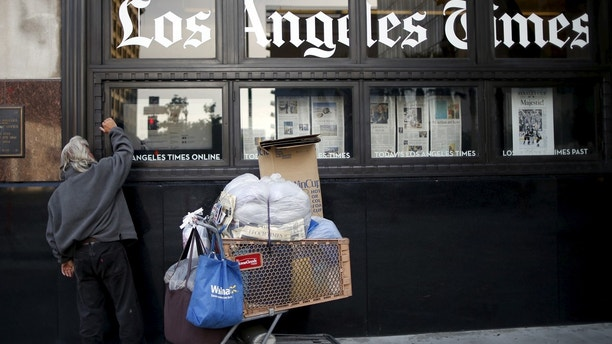 A homeless man reads the Los Angeles Times in the window of the building of Los Angeles Times newspaper, which is owned by Tribune Publishing Co, in Los Angeles, California, U.S., April 27, 2016. REUTERS/Lucy Nicholson - GF10000397617
