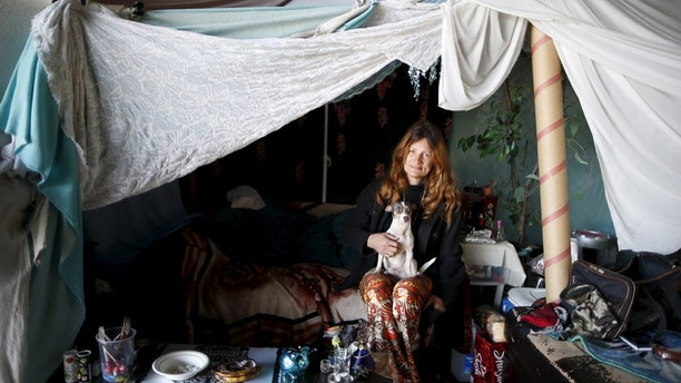 "Karen Souza, 55, poses for a portrait with her dog Handsome by the tent in which she lives, under a freeway on a street in Los Angeles, California, United States, November 13, 2015. Souza has been homeless for a decade, and has known Kathleen Fox for 20 years. She originally became homeless after her spouse was arrested, ""my whole world crumbled, my teenagers ran out of control and it just got bad"". REUTERS/Lucy Nicholson PICTURE 7 OF 17 - SEARCH ""NICHOLSON MOTORHOME"" FOR ALL IMAGES TPX IMAGES OF THE DAY - GF10000270547"
