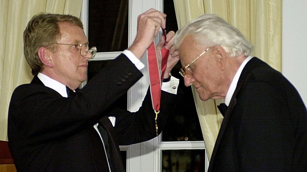 U.S. evangelist Billy Graham (R) receives a medal as he is presented