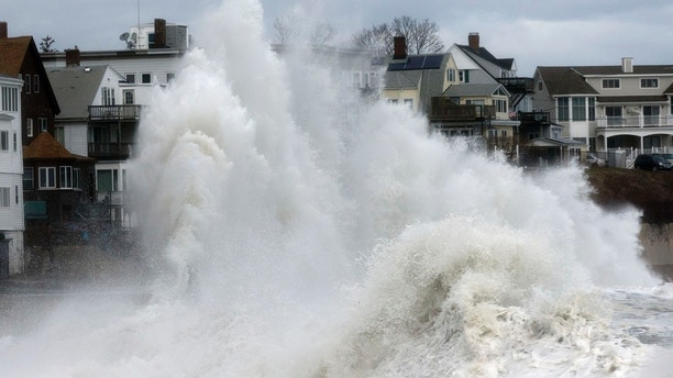 A large wave crashes into a seawall in Winthrop, Mass., Saturday, March 3, 2018, a day after a nor'easter pounded the Atlantic coast. Officials in eastern Massachusetts, where dozens of people were rescued from high waters overnight, warned of another round of flooding during high tides expected at midday. (AP Photo/Michael Dwyer)