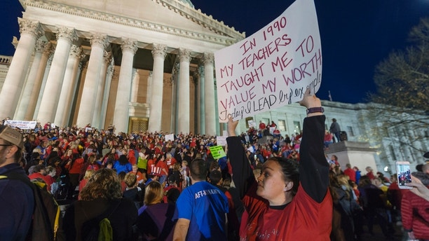 FILE - In this Feb. 27, 2018, photo, Jennyerin Steele Staats, a special education teacher from Jackson County holds her sign aloft outside of the capitol building after WVEA President Dale Lee outlined the terms for ending the walkout on the fourth day of statewide walkouts in Charleston, W.Va. Unions representing West Virginia teachers and service personnel said Saturday, March 3, that they will stay out on strike after the state Senate voted to cut the 5 percent pay raise they had negotiated with Gov. Jim Justice. (Craig Hudson/Charleston Gazette-Mail via AP, File)