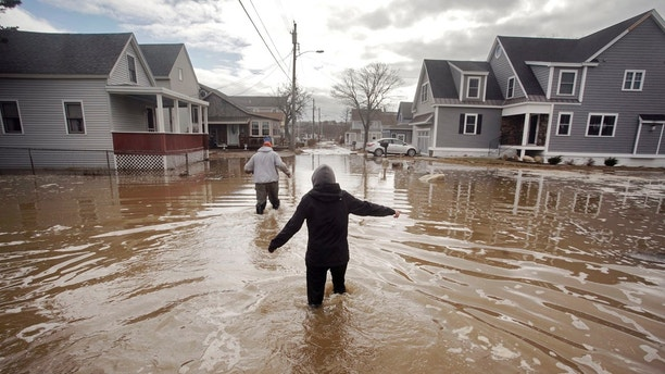 Kaylee Collin, right, and Spencer Stone walk through water along North Avenue in Camp Ellis in Saco, Maine on Sunday, March 4, 2018. The coastal neighborhood as well as other parts of the southern Maine coast were flooded for the third day in a row on Sunday. (Gregory Rec/Portland Press Herald via AP)