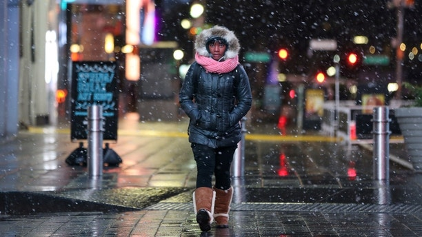 A woman walks as snow falls in Times Square in Manhattan in New York City, New York, U.S., March 7, 2018. REUTERS/Amr Alfiky - RC1642A41440
