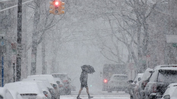 A man crosses the street through heavy snow in Hoboken, N.J., Wednesday, March 7, 2018. (AP Photo/Seth Wenig)