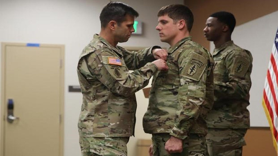 Brig. Gen. Richard Angle pins the Soldier's Medal on Staff Sgt. Adams on Monday.