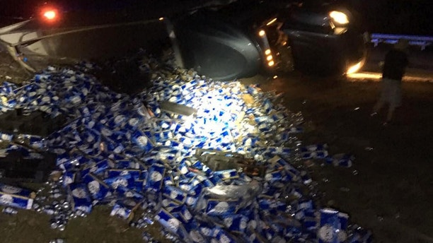 Semi overturns, beer thrown from trailer