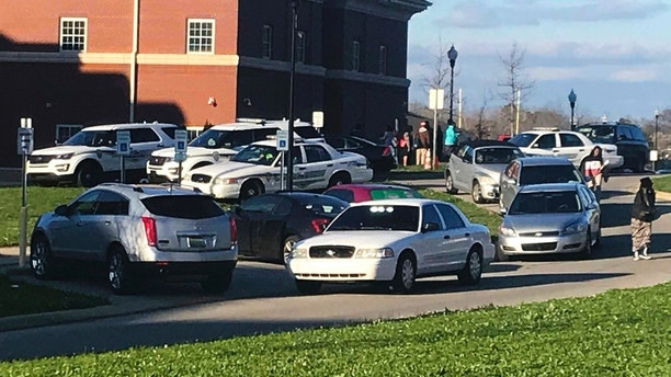 Authorities investigate the scene where a shooting occurred at Huffman High School, Wednesday, March 7, 2018, in Birmingham, Ala. Birmingham Interim Police Chief Orlando Wilson said at a news conference that authorities are seeking to determine whether the deadly shooting Wednesday at the Alabama high school was accidental or if a gun since recovered by investigators was intentionally discharged. (Carol Robinson/AL.com via AP)