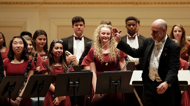 Members of the Marjory Stoneman Douglas High School Wind Symphony stand to receive applause after a performance at Carnegie Hall in New York, Tuesday, March 6, 2018. Three weeks after a gunman killed 17 people at their high school, the students from Parkland, Fla., followed through with a long-planned Carnegie Hall performance. (AP Photo/Seth Wenig)