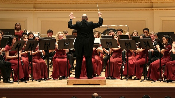 The Marjory Stoneman Douglas High School Wind Symphony performs at Carnegie Hall in New York, Tuesday, March 6, 2018. Three weeks after a gunman killed 17 people at their high school, the students from Parkland, Fla., followed through with a long-planned Carnegie Hall performance. (AP Photo/Seth Wenig)